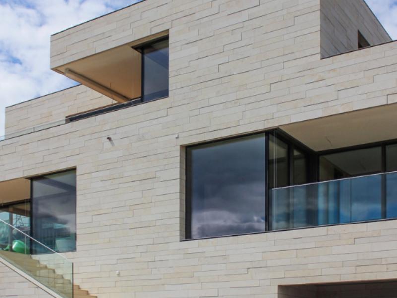 Фото облицовка фасада натуральным бежевым камнем